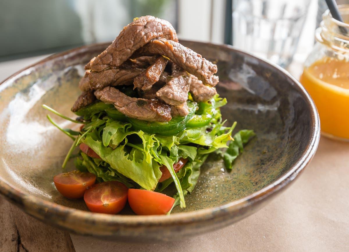 Teller mit hoch geschichtetem Salat und Fleischtopping