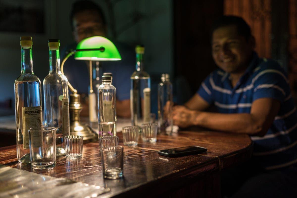 Shotgläser auf brauner Bartheke mit lachendem Mexikaner im Hintergrund