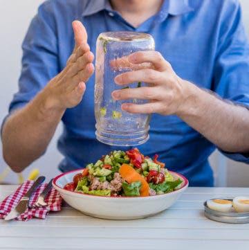 Mann leert gefülltes Glas über Schüssel aus