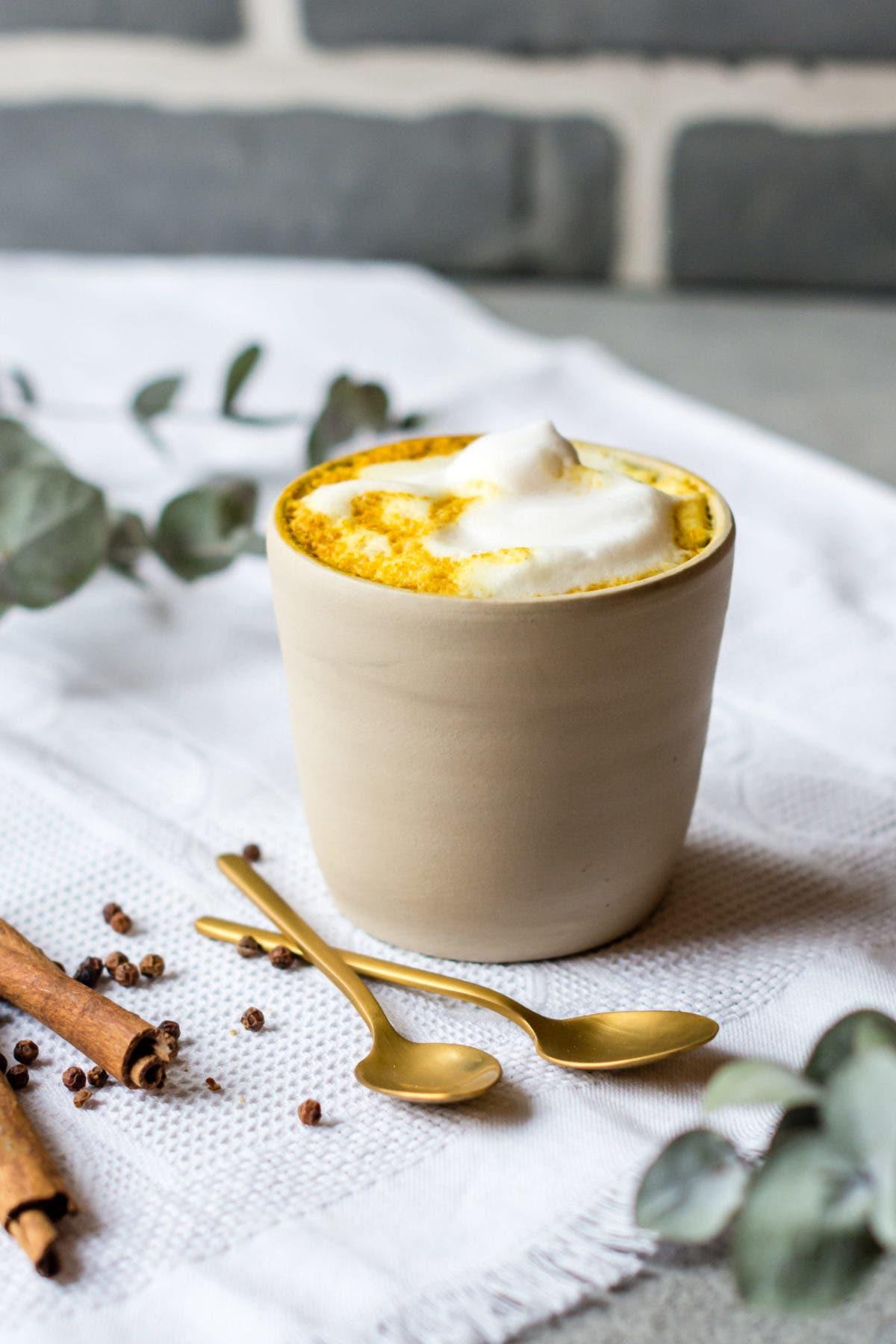 Keramikbecher mit Kurkuma Latte und Milchschaum.