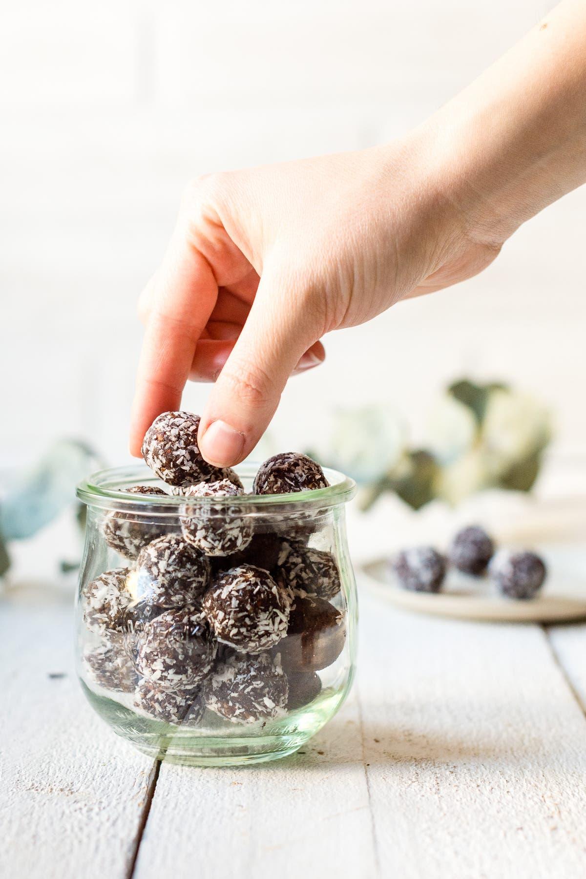 Glas gefüllt mit Schokoladen Kokos Bliss Balls. Hand hält ein Energiebällchen fest.