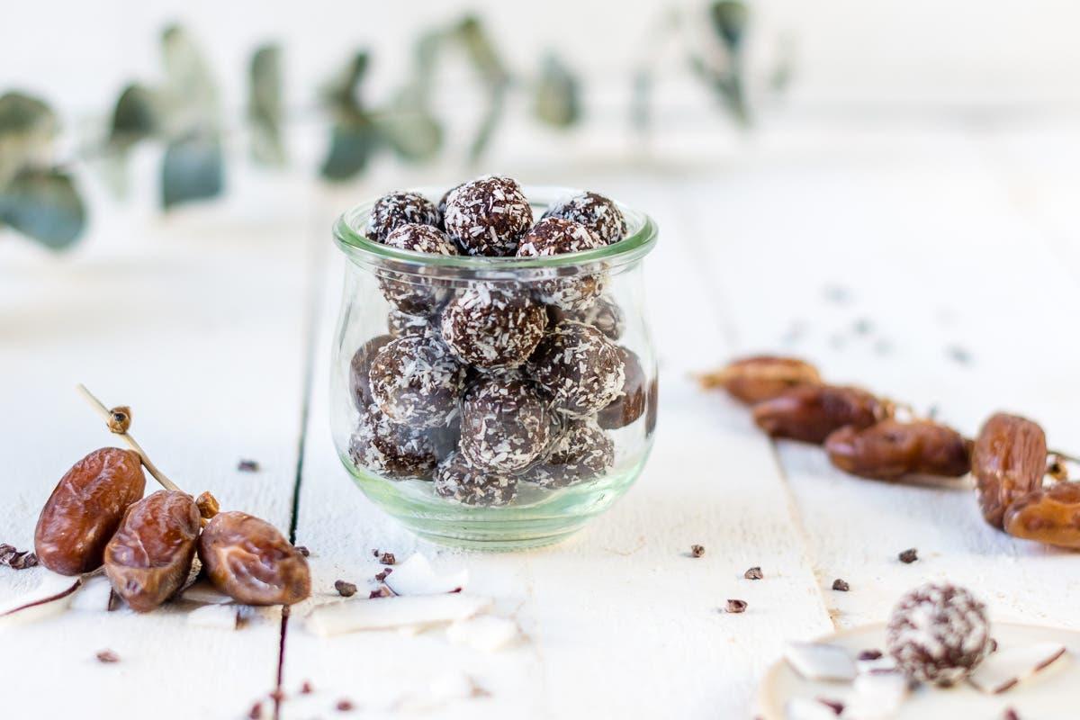 Glas gefüllt mit Schokoladen Bliss Balls und Kokosstreuseln auf weißem Untergrund und Datteln daneben.