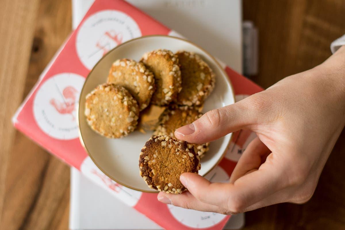 Hand greift Keks von Keksteller