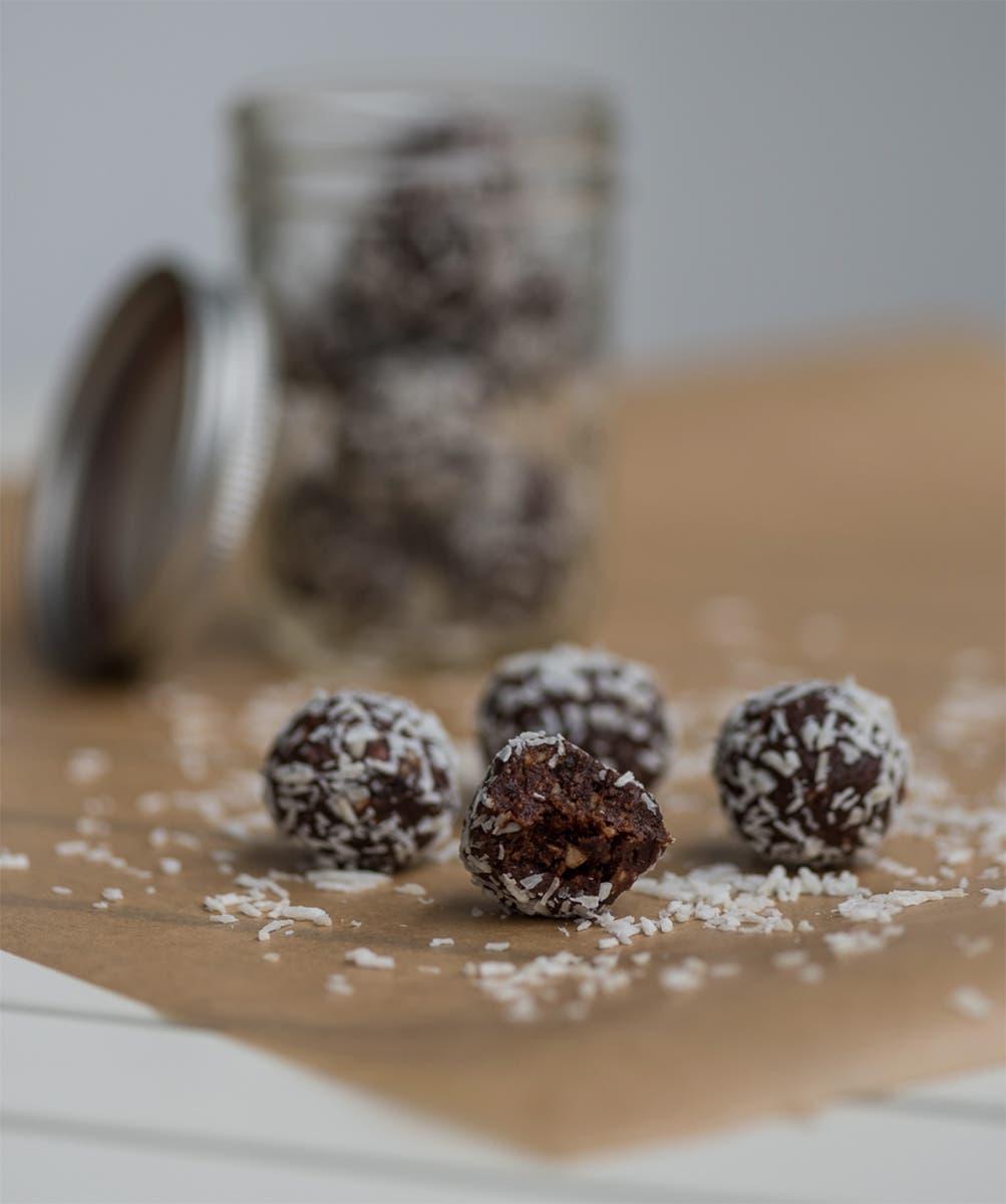 Vier schokoladige Bliss Balls mit Kokosflocken vor Glas