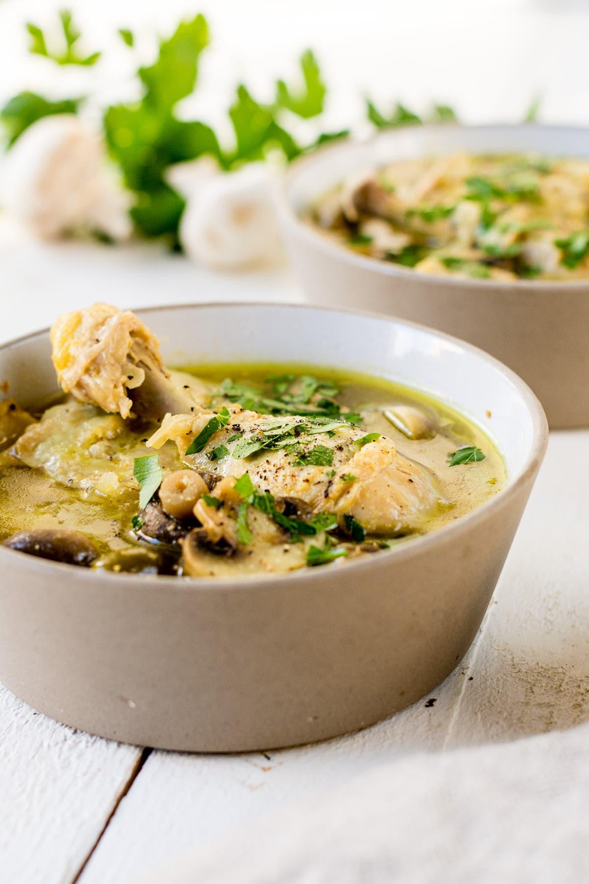 Hühnerbrühe mit Pilzen und Hähnchenschenkeln in zwei Schüsseln.
