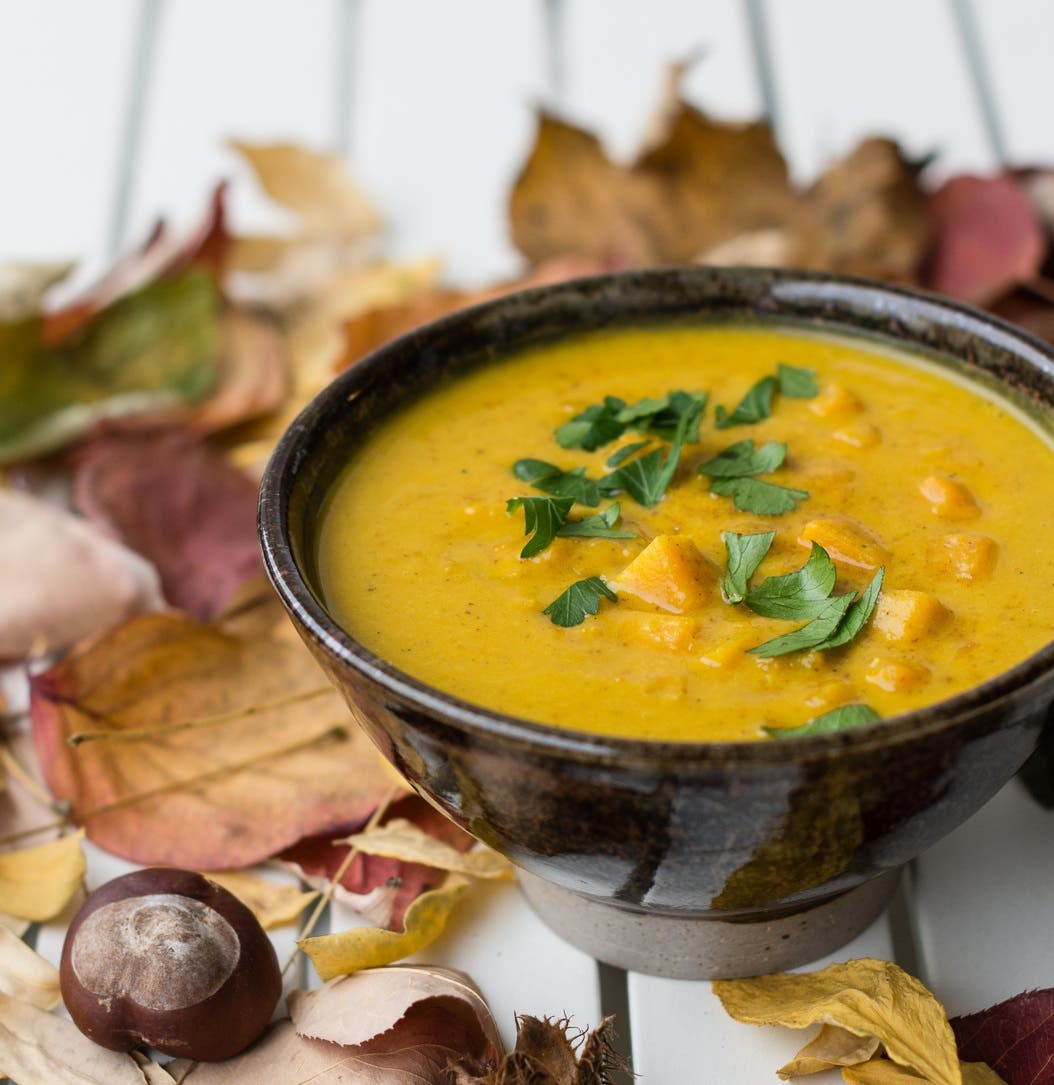 Gelbe Suppe in brauner Schale mit Petersilie garniert und auf Tisch mit Herbstblättern dekoriert