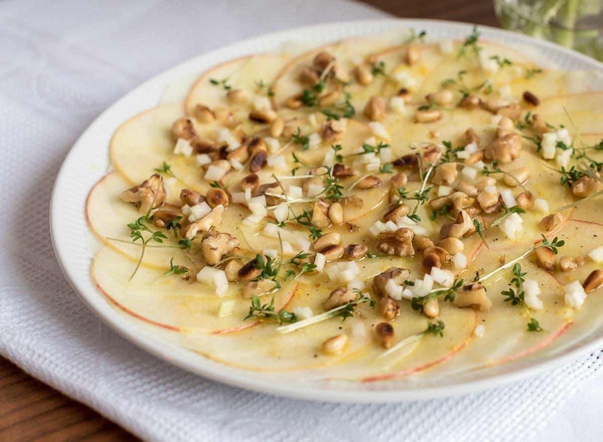 Kohlrabi-Apfel-Carpaccio auf weißem Teller mit Pinienkernen und Kresse