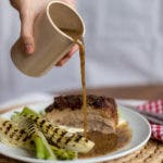 Hand gießt dunkle Soße über Teller mit Fenchel und Fleisch