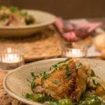 seitliche Ansicht von gedecktem Tisch mit Tellern mit knusprigem Hähnchen und Petersilie