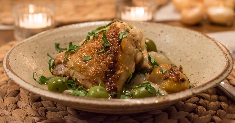 Knuspriges Hähnchen mit Oliven und Petersilie auf Teller angerichet