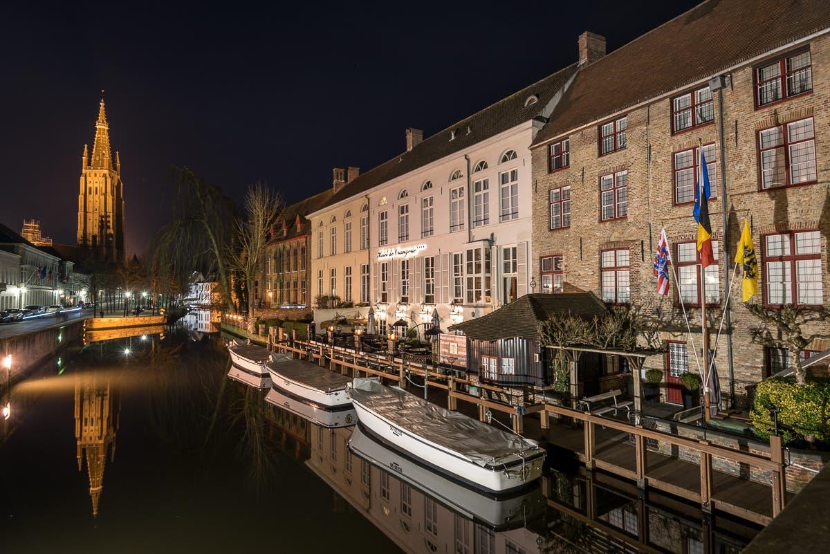 Kanal von Brügge bei Nacht mit beleuchtetem Kirchturm
