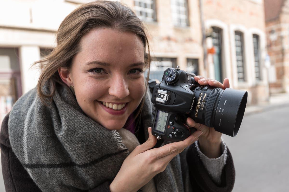 Portrait von lachender Frau mit Kamera in den Händen