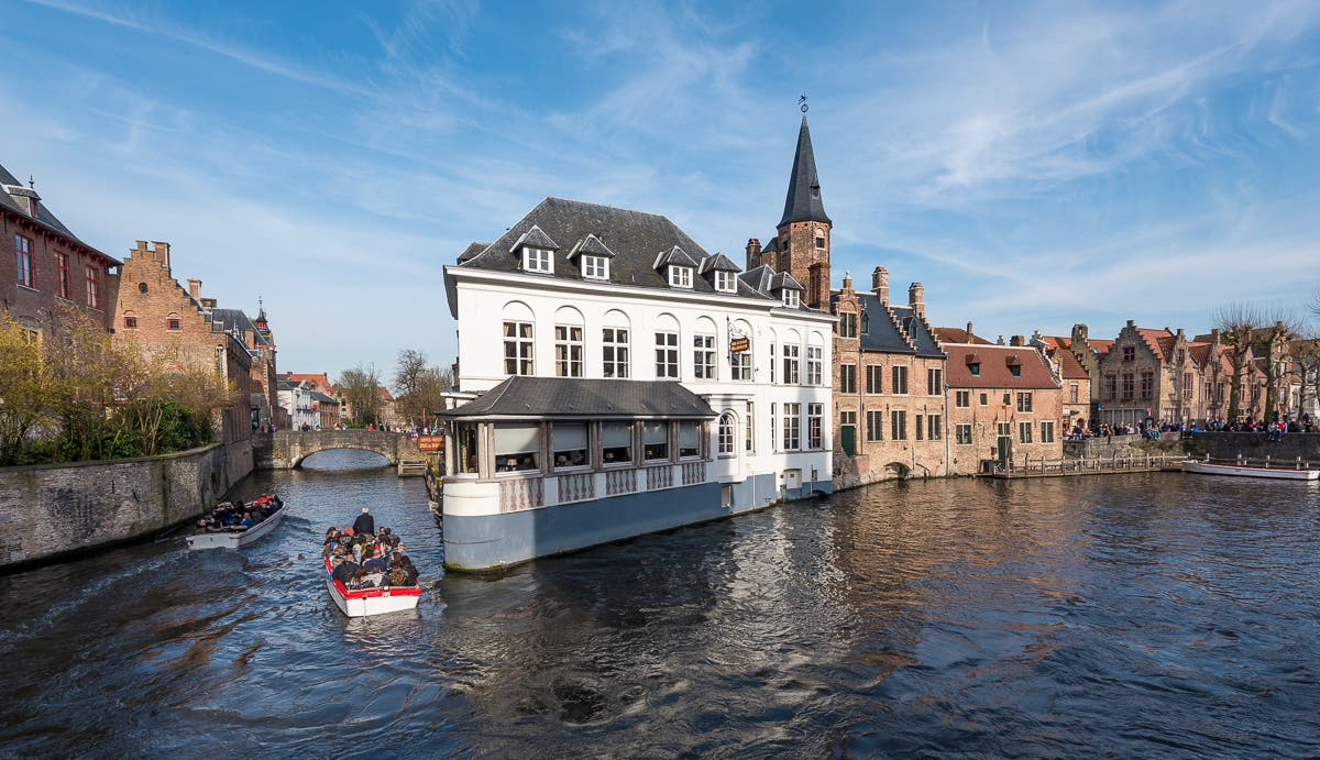 Weitwinkelaufnahme von Kanal zwischen Häusern in Brügge mit kleinem Boot