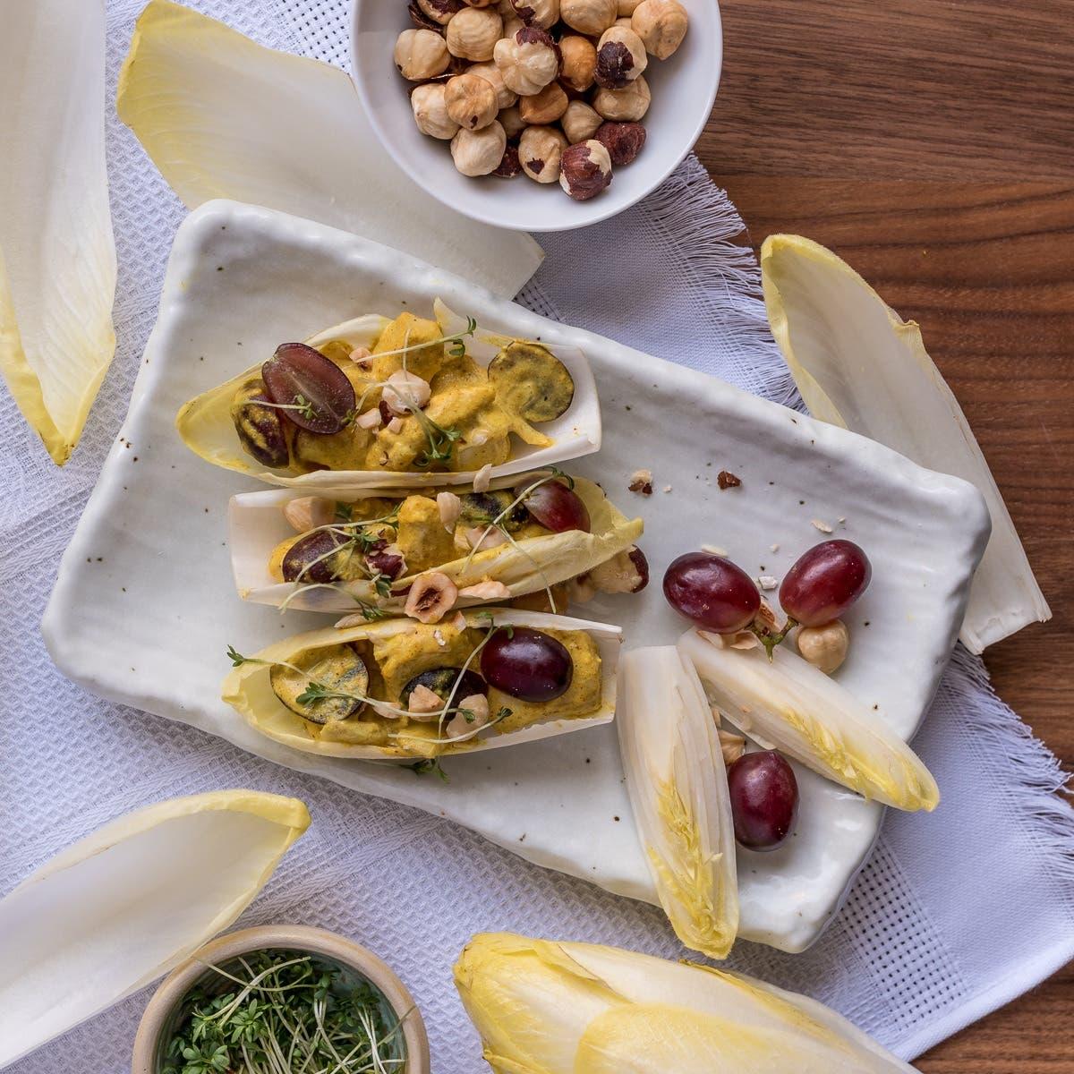 Topshot von weißer Keramikplatte mit Chicoree Schiffchen, garniert mit Trauben und Haselnüssen