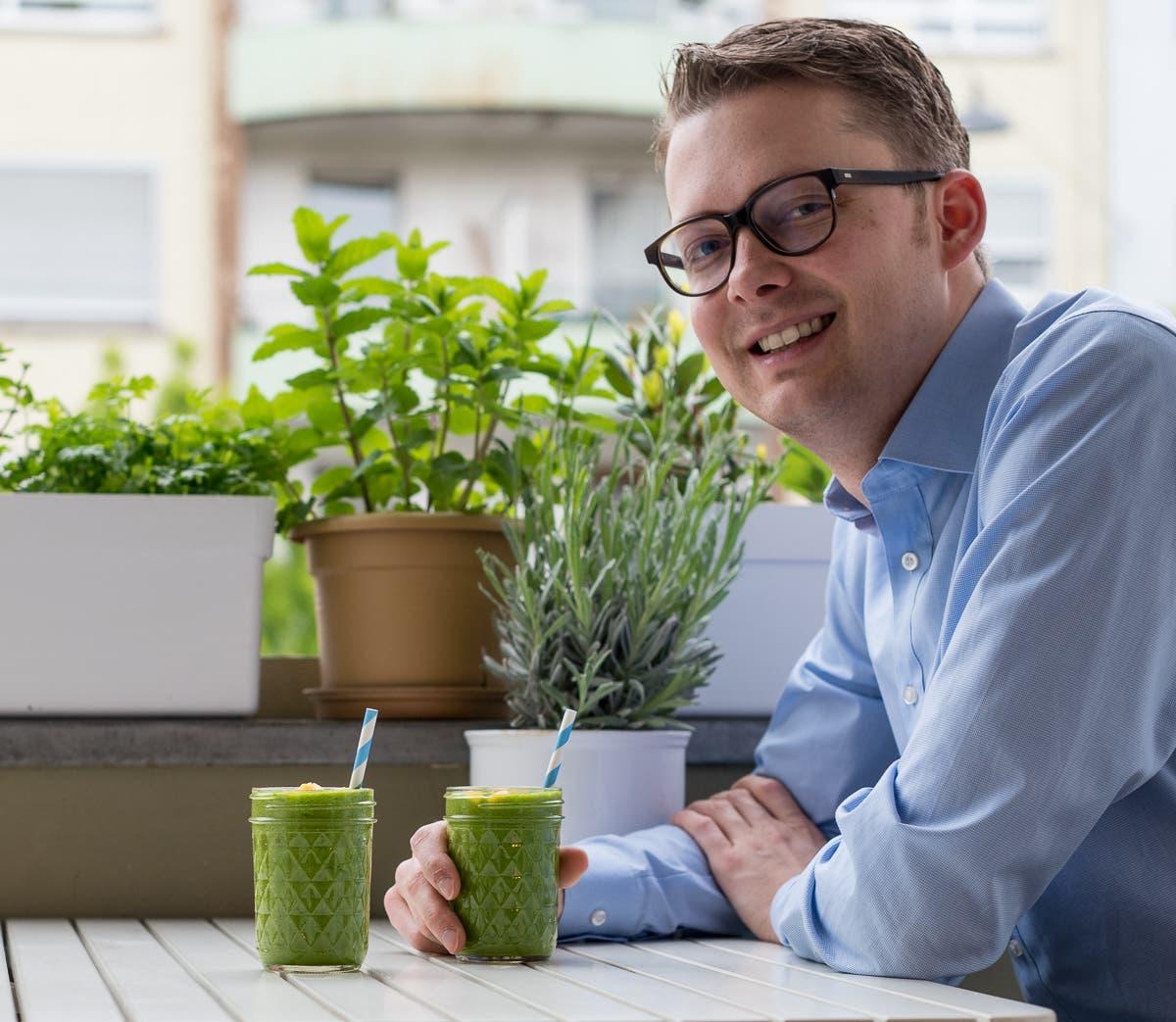 Mann an Tisch sitzend mit grünem Smoothie in der Hand