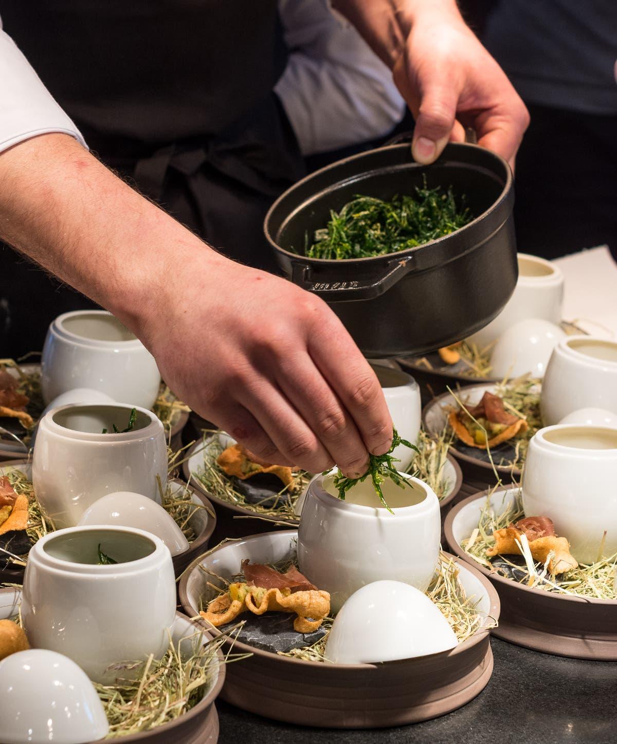 Hand füllt weiße Behälter auf Teller mit Gerichten