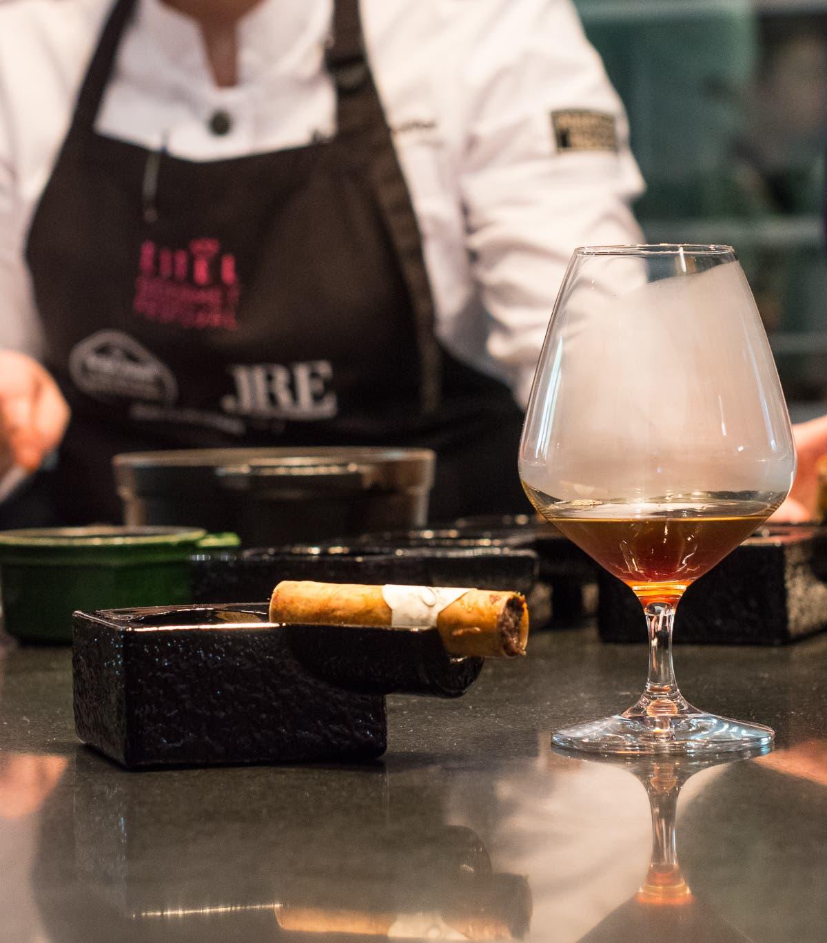 Goldene Flüssigkeit in Weinglas mit daneben liegendem Gebäck, das an Zigarre erinnert