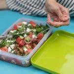 Brotdose mit bunten Salat und Händen mit Messer und Gabel