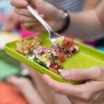 Hand hält knallgrünen Teller mit buntem Salat darauf