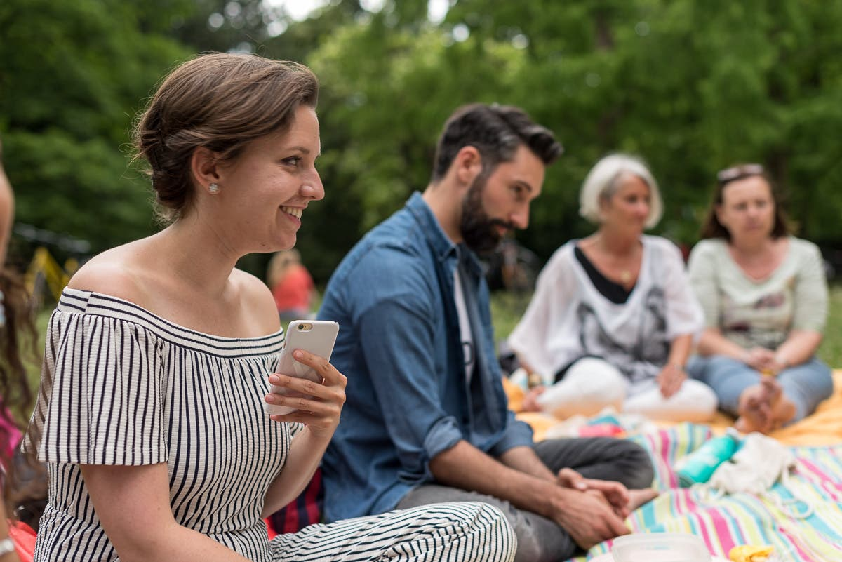lächelnde Frau sitzend mit Handy in der Hand und gestreiftem Outfit