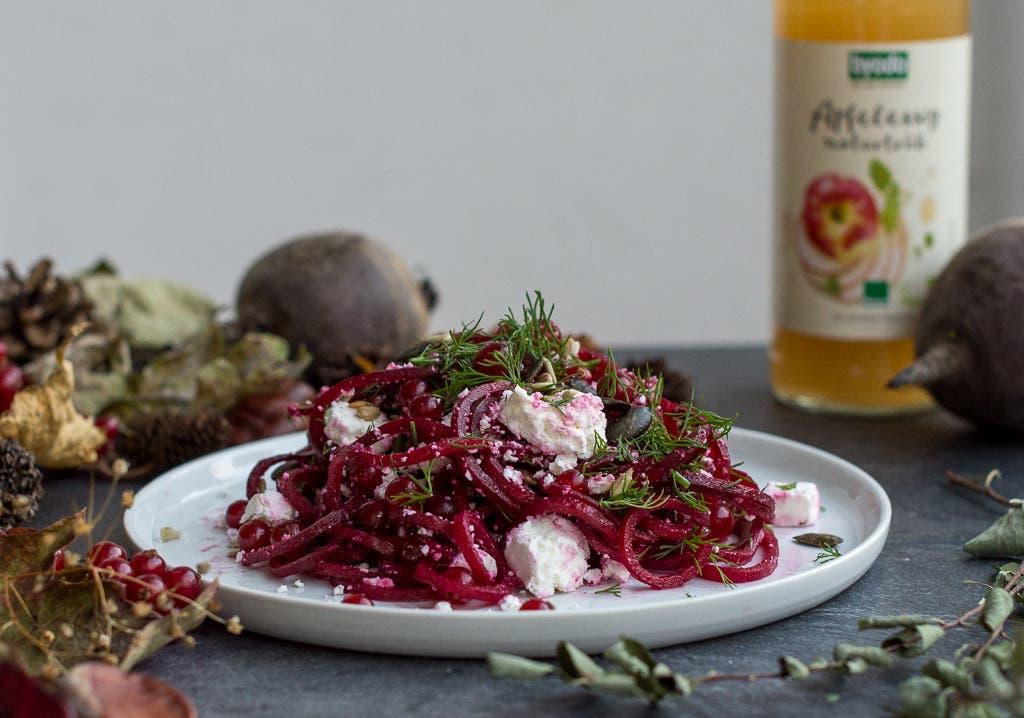 Rote Bete Salat auf weißem Teller vor Apfelessigflasche