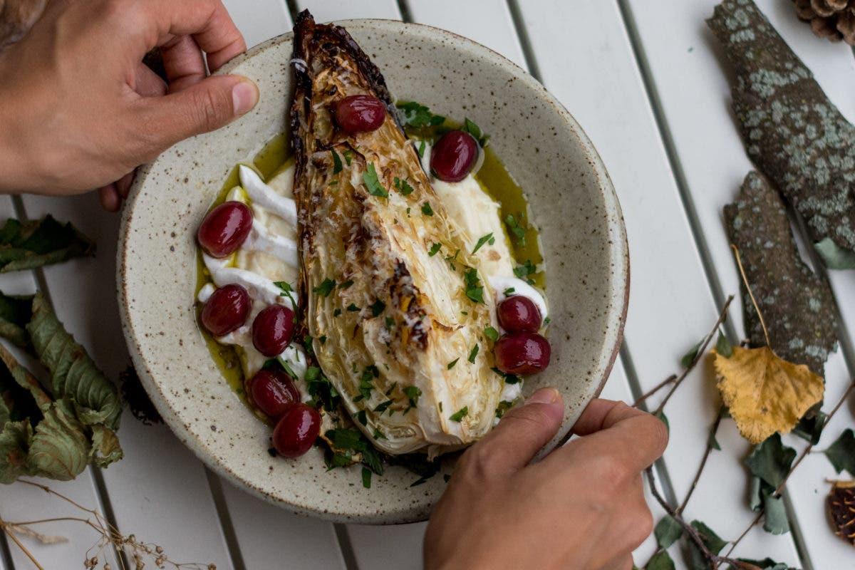Zwei Hände greifen Teller mit Spitzkohl, Selleriepüree, roten Trauben und Petersilie auf weißem Tisch mit Herbstdeko
