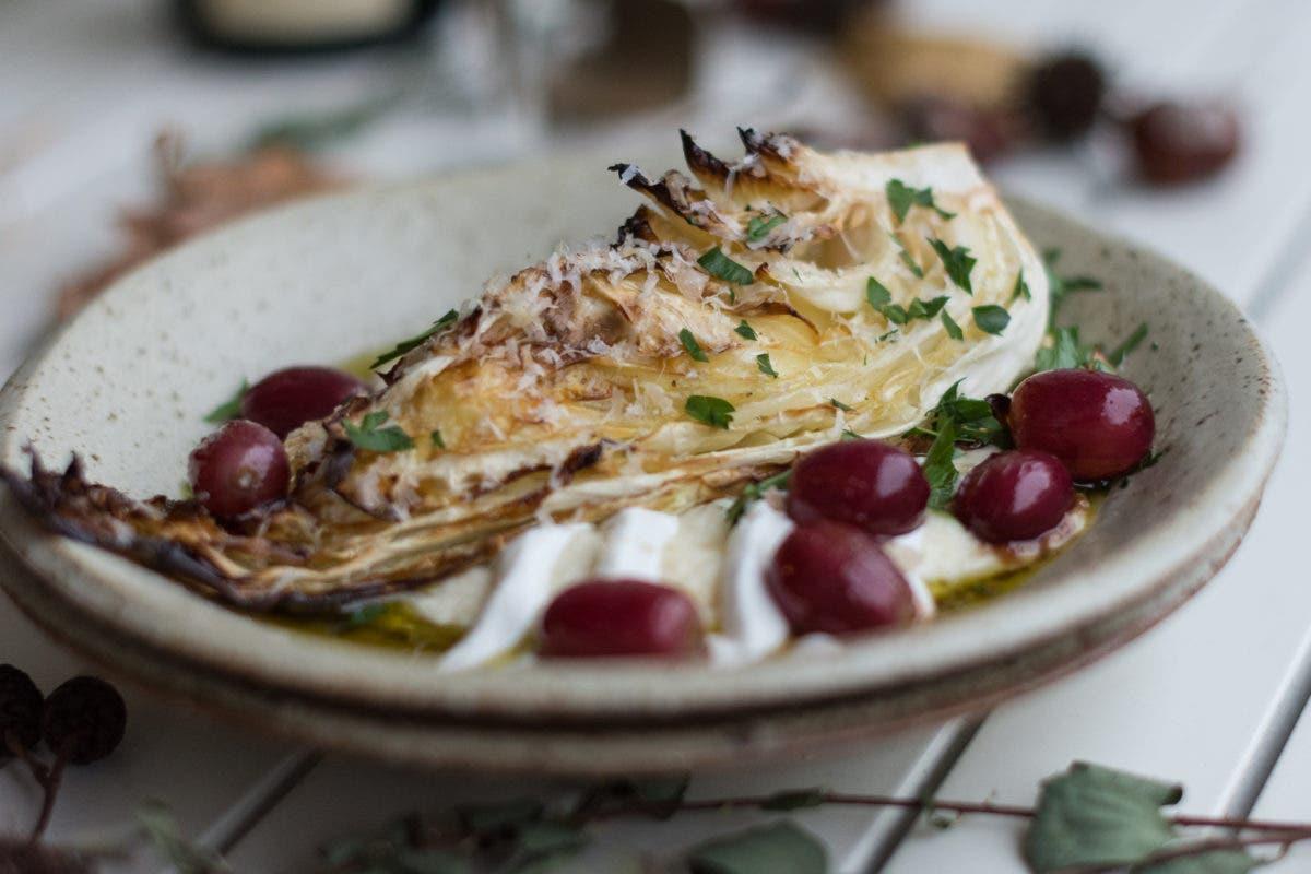 Close Up von geschmortem Spitzkohl mit roten Trauben, Petersilie auf weißem Tisch