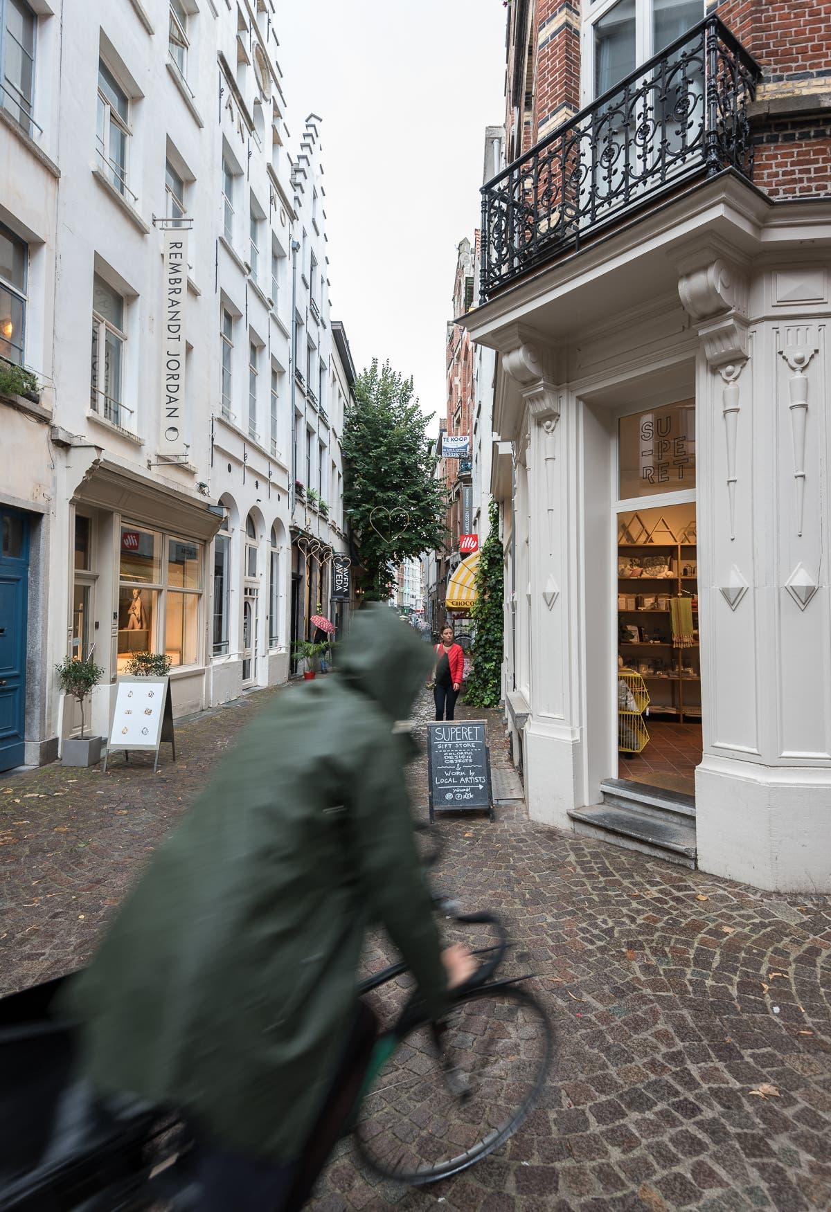 kleine Straße von Antwerpen mit vorbeifahrendem Radfahrer