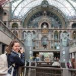 Bahnhof Antwerpen mit Frau, die über Schulter schaut