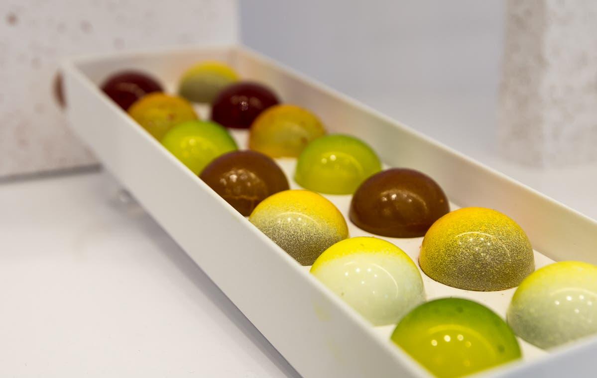 grün, gelb und braune belgische Schokoladenkugeln in Reihen angeordnet