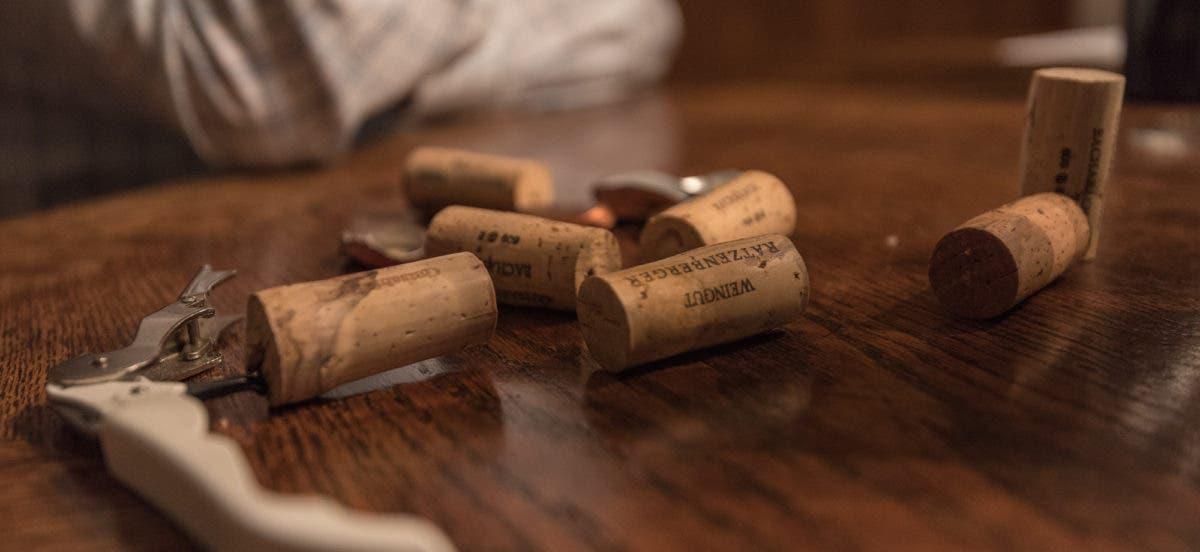 sieben Weinkorken auf Tisch liegend mit Weinöffner