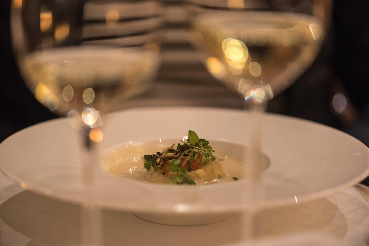 Aufnahme von Teller mit angerichtetem Essen und zwei Weißweingläsern