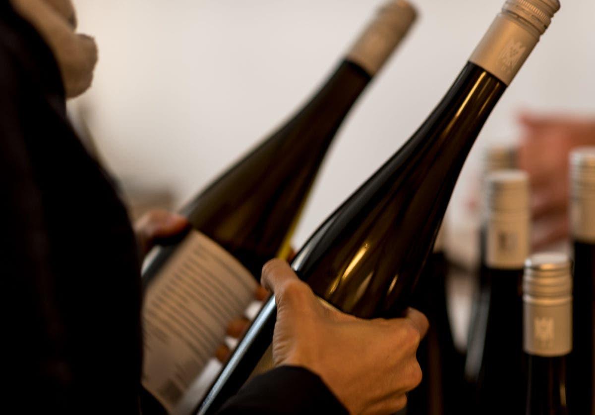 Zwei Hände halten dunkle Weinflaschen