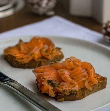 Zwei Scheiben Brot mit Lachs belegt auf weißem Teller