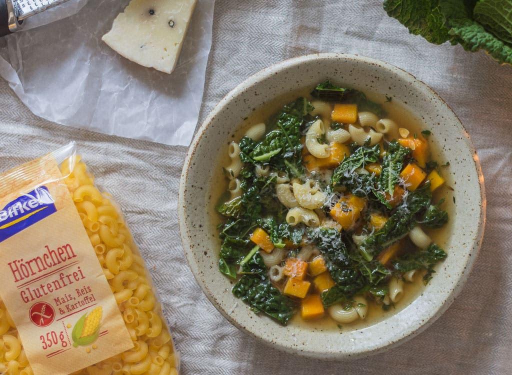 Top Shot von Suppenteller mit klarer Brühe und Suppeneinlage, daneben ein Stück Käse und eine Packung Nudeln