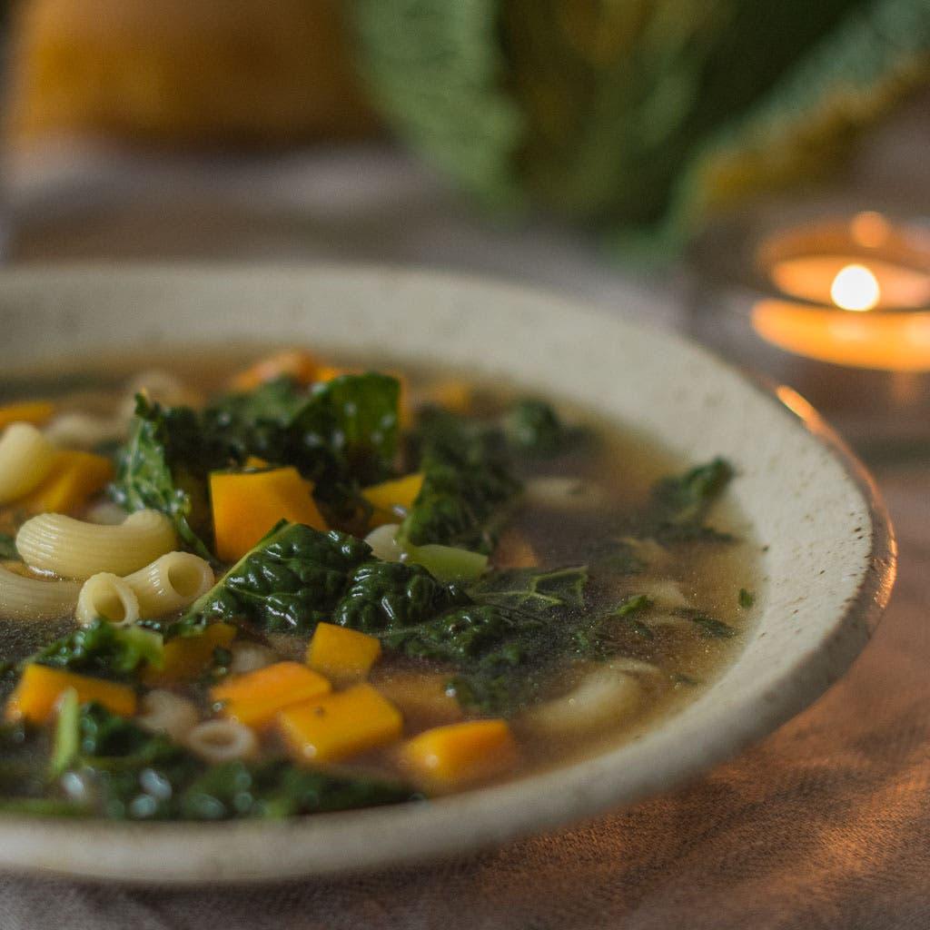 Seitliches Close Up von Suppenteller mit klarer Brühe und Suppeneinlage