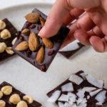 Hand hält ein Stück selbstgemachte Schokolade mit Nüssen und Beeren fest.