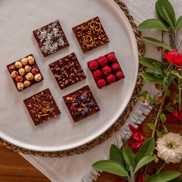 Topshot von weißem Teller mit sieben Schokoladenquadraten und verschiedenen Toppings