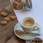 Espresso in weißer Tasse und mit kleinem Teelöffel und Amarettini Keks