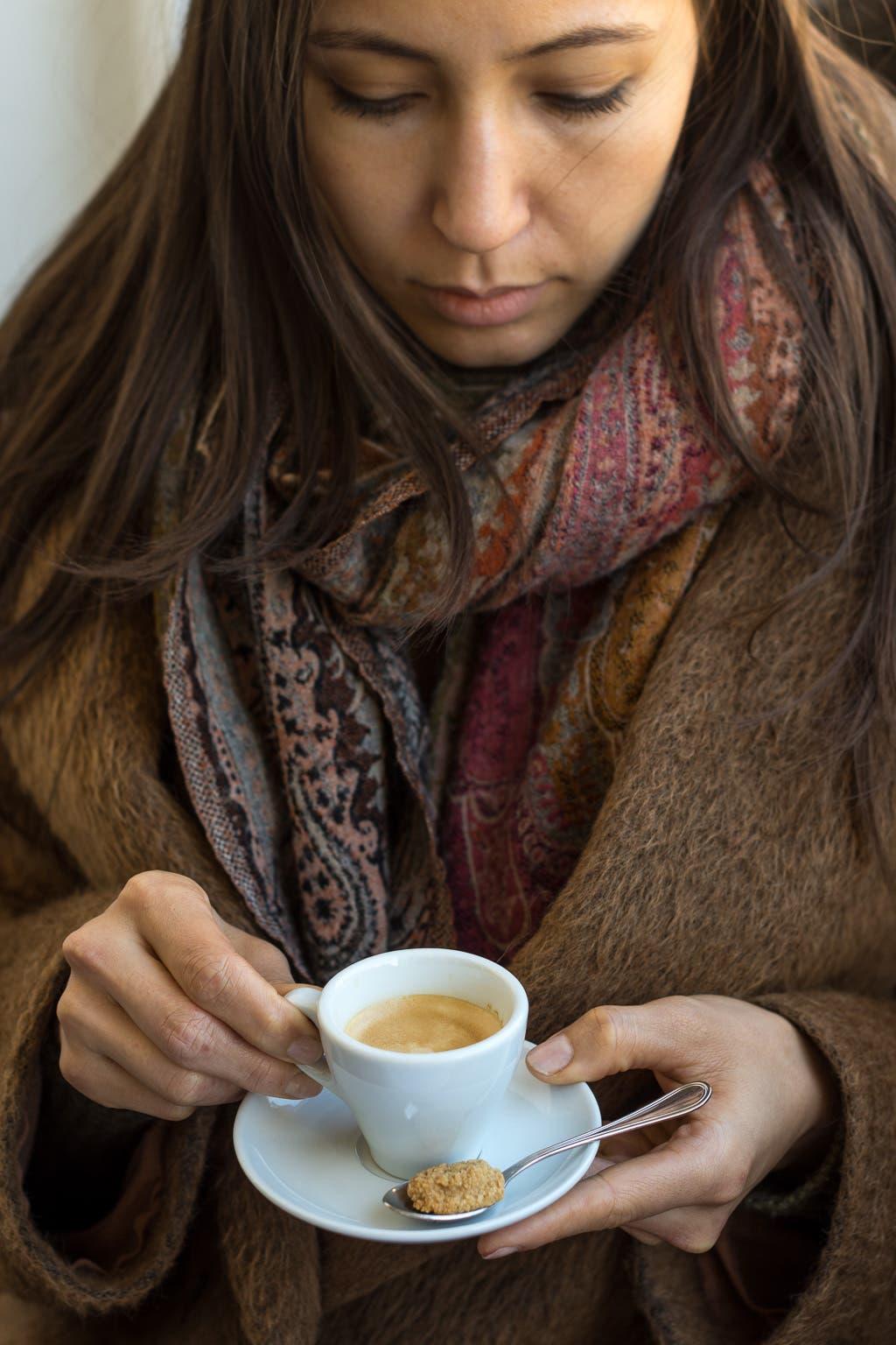 Frau hält Espresso mit kleinem Amarettini in der Hand