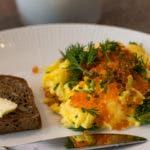 Rührei mit Fischrogen und Dill auf Teller mit Brot