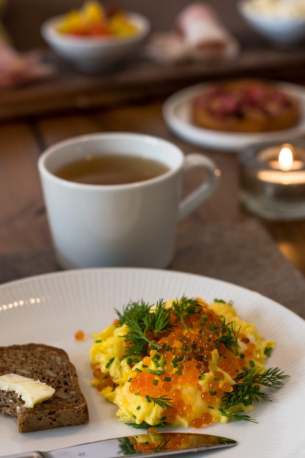 Teller mit Rührei, Fischrogen und einer Scheibe Brot vor einer Tasse Tee