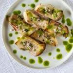 Gegrillte Pilze auf weißem Teller mit grüner Sauce
