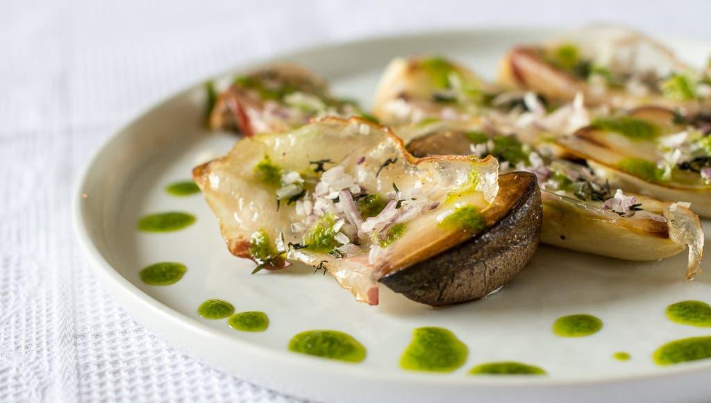 Gegrillter Kräutersaitling mit grüner Sauce auf weißem Teller