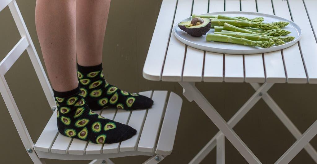 Stuhl mit daraufstehender Person mit bedruckten Socken und Tisch mit angerichtetem Teller