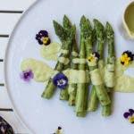 Grüner Spargel auf weißem Teller mit heller Sauce und Blumen
