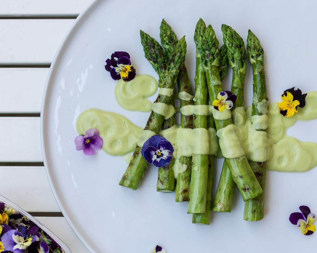 Grüner Spargel auf weißem Teller mit Sauce und Blumen angerichtet