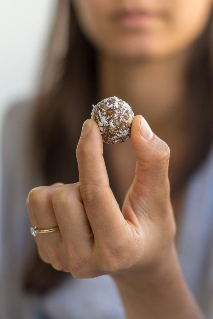 Hand hält kleine Snackkugel mit Kokosraspeln in den Fingern