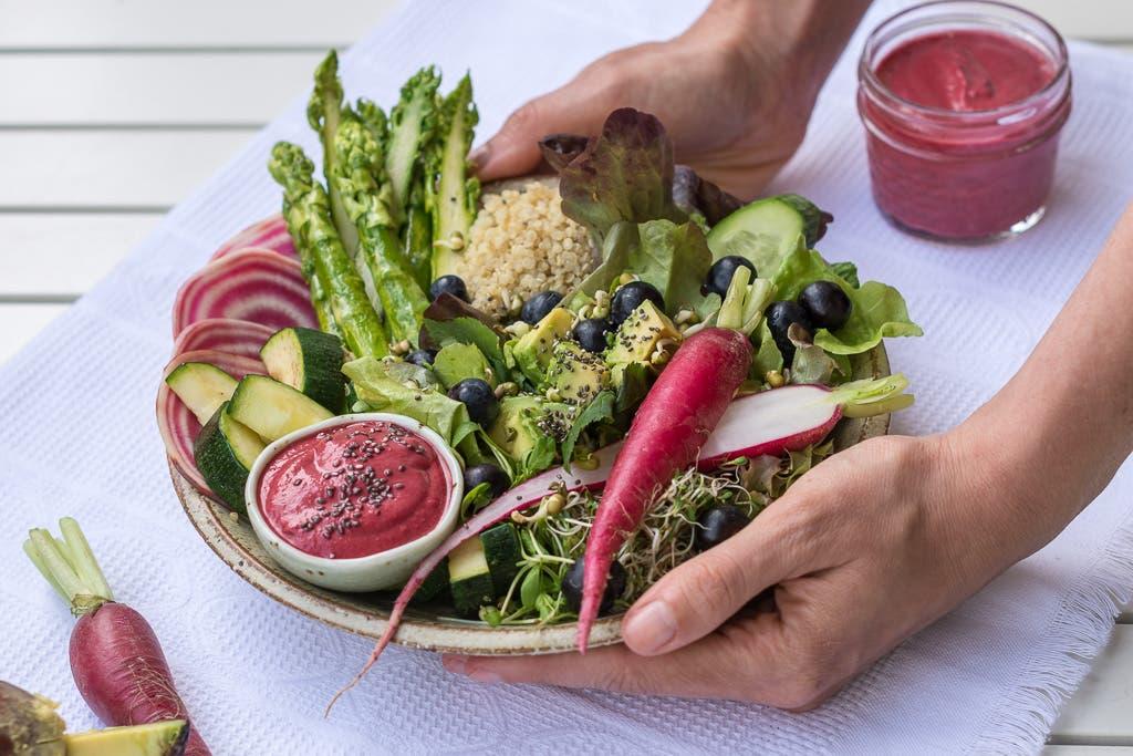 Buddha Bowl mit grünem Gemüse und pinken Akzenten