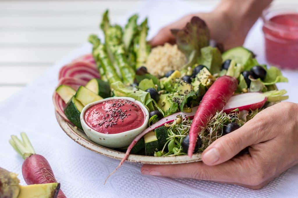seitliche Ansicht von Buddha Bowl grünem Gemüse und pinken Akzenten